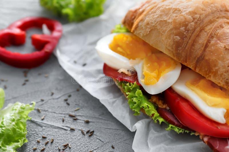 Smakelijke croissantsandwich met gekookt ei op grijze lijst stock foto