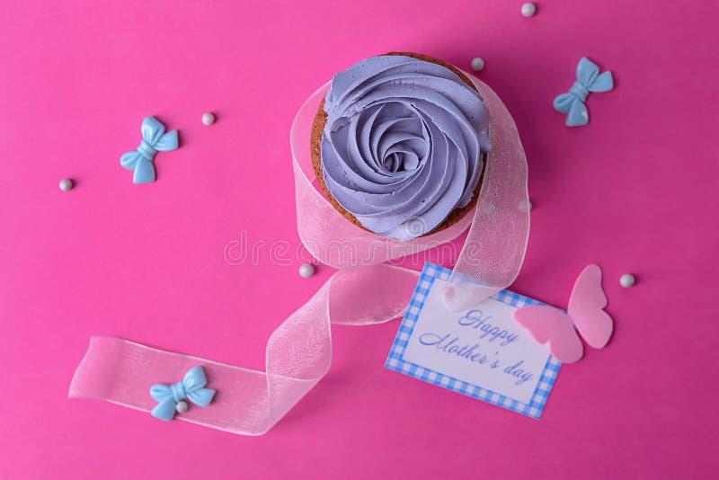 Smakelijke cupcake en kaart met de DAG van de woorden GELUKKIGE MOEDER \ 'S op kleurenachtergrond royalty-vrije stock foto's