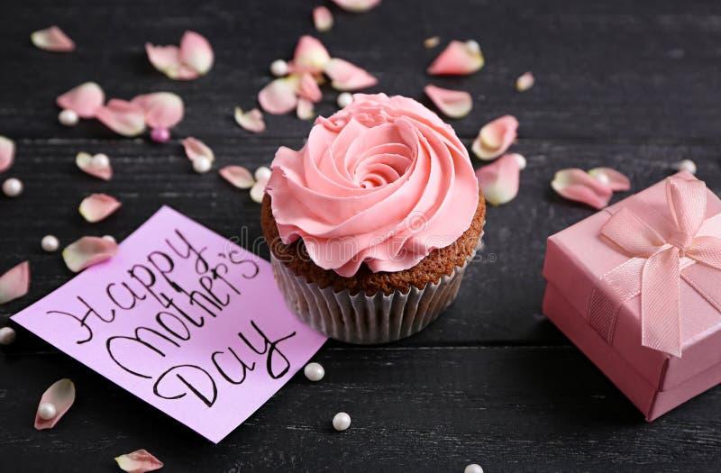 Smakelijke cupcake met kaart en giftvakje voor Moederdag op lijst royalty-vrije stock foto's