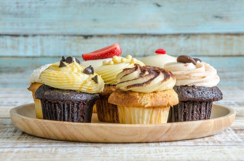 Smakelijke cupcake op houten lijst aangaande uitstekende achtergrond stock foto