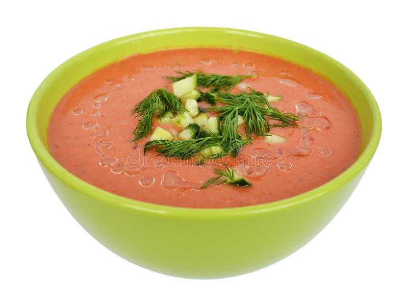 Smakelijke die gazpacho met gehakte komkommers en dille in een groene kom wordt bestrooid, voor-aan-hoogste die mening, op witte  royalty-vrije stock fotografie