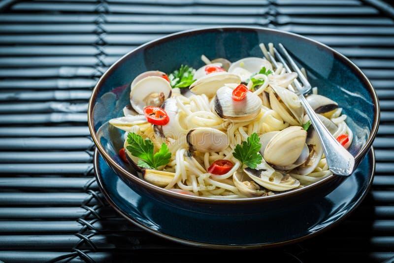 Smakelijke die zeevruchtendeegwaren van tweekleppige schelpdieren, peper en peterselie worden gemaakt stock fotografie