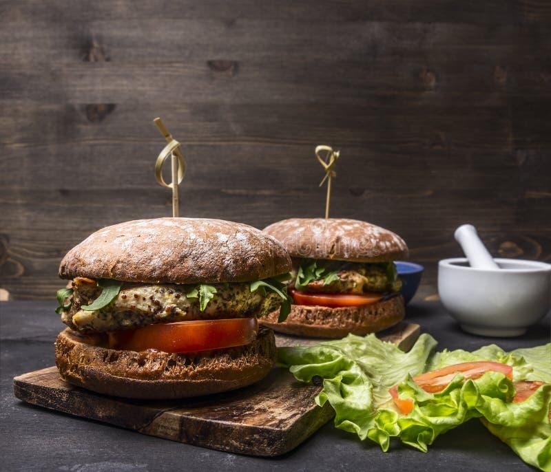 Smakelijke eigengemaakte burgers met kip in mosterdsaus met arugula en kruiden op een scherp gebied van de raadstekst op houten r royalty-vrije stock afbeeldingen
