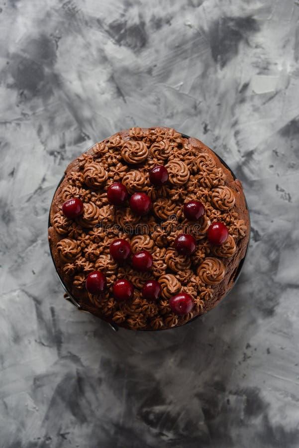 Smakelijke eigengemaakte chocoladecake met chocoladesuikerglazuur en ruwe kersen op donkere concrete minimalistische stijl als ac royalty-vrije stock fotografie