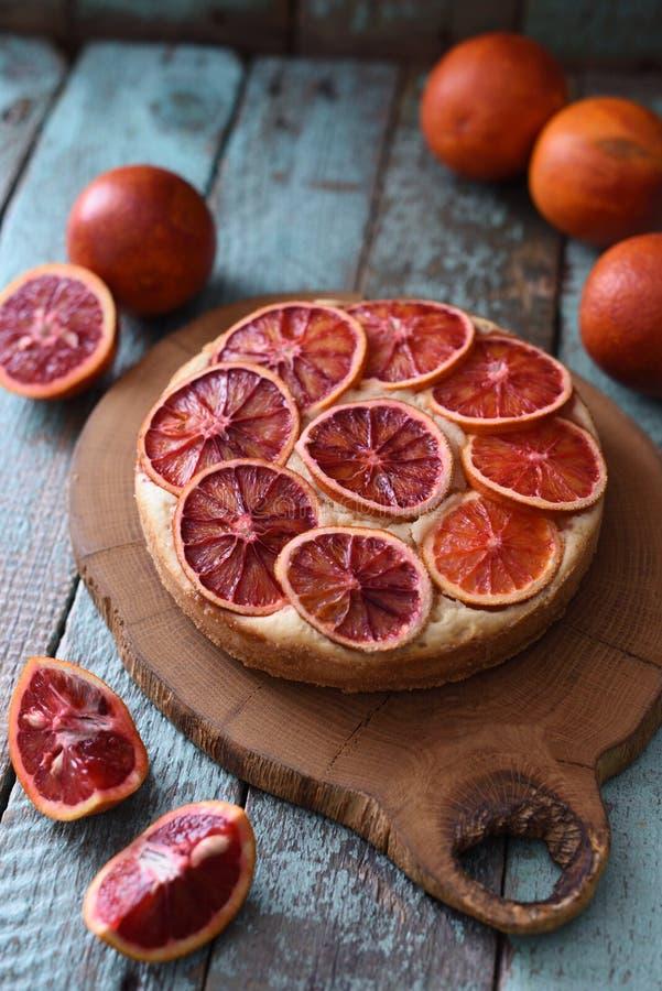 Smakelijke eigengemaakte die cake met de plakken van de bloedsinaasappel met ruwe blo worden gediend stock fotografie