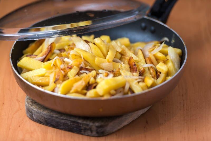 Smakelijke eigengemaakte gebraden die aardappels met uien in een pan worden gediend stock foto's