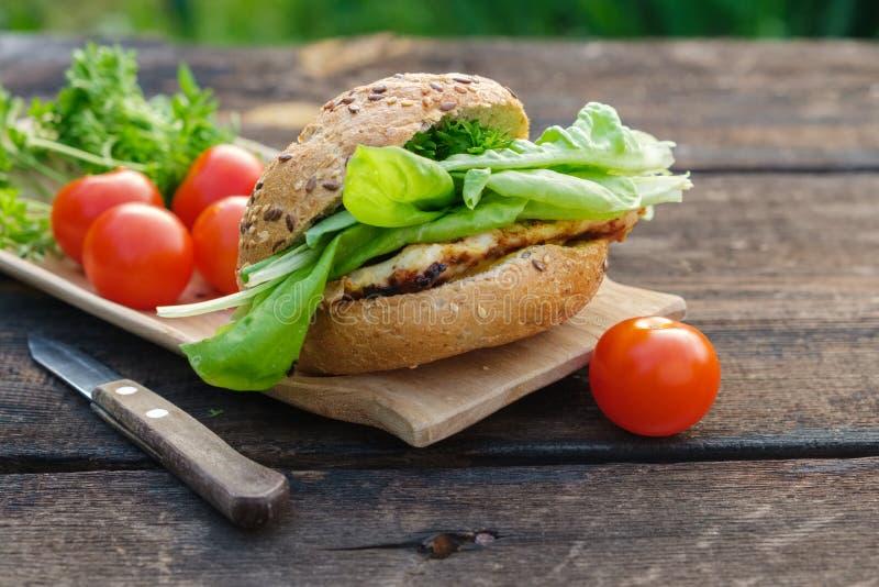 Smakelijke eigengemaakte hamburger en sla, tomaten op houten picknicklijst royalty-vrije stock afbeelding