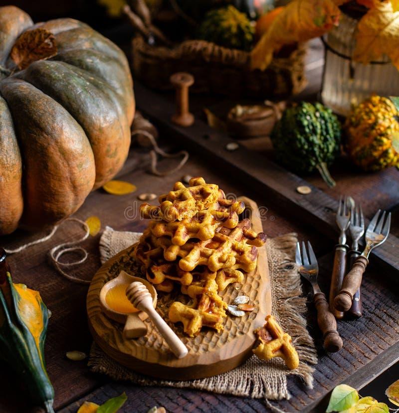 Smakelijke eigengemaakte pompoen oranje wafels op houten raad op bruine rustieke lijst met pompoenen royalty-vrije stock foto