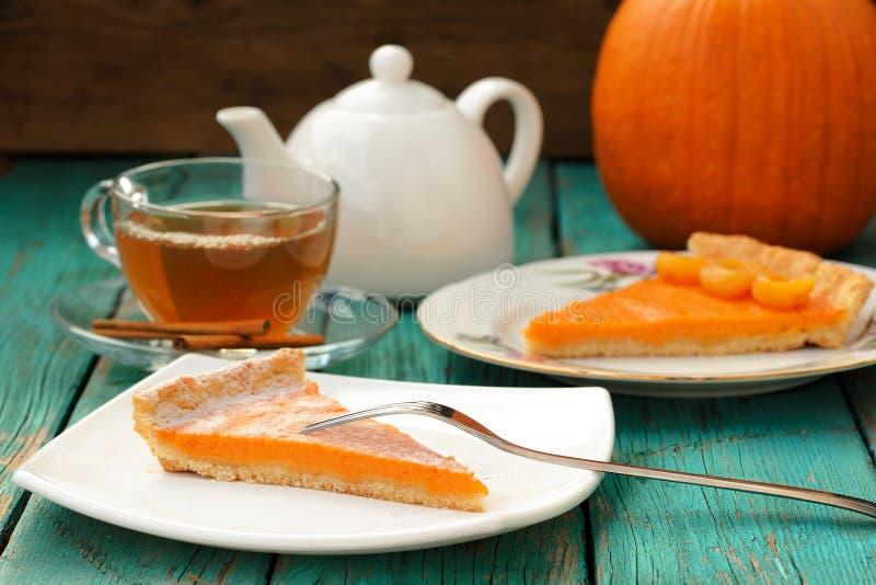 Smakelijke eigengemaakte pompoenpastei met gesneden stuk, thee in glaskop, whi stock fotografie