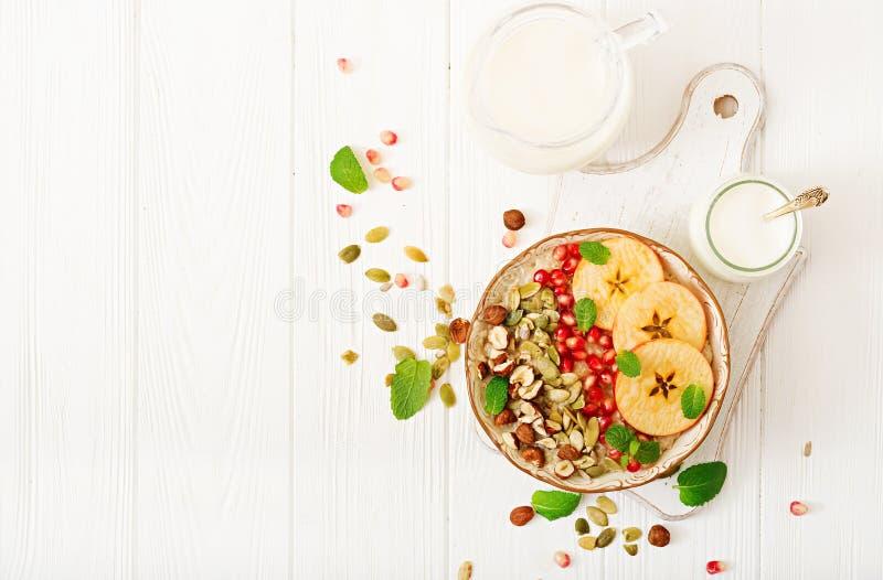 Smakelijke en gezonde havermeelhavermoutpap met appelen, granaatappel en noten royalty-vrije stock afbeeldingen