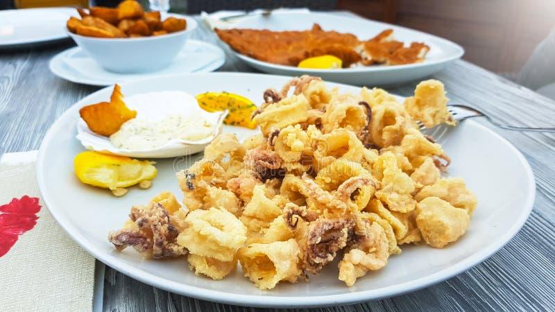 Smakelijke en knapperige gebraden pijlinktvissen op een witte plaat en een houten die lijst met mayonaisesaus met verse citroen w stock afbeeldingen