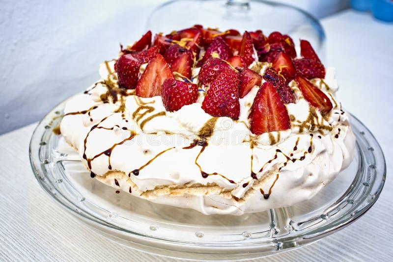 Smakelijke en mooie die schuimgebakjecake met rode die aardbeien wordt verfraaid in de helft worden en met vloeibare karamel word royalty-vrije stock afbeeldingen