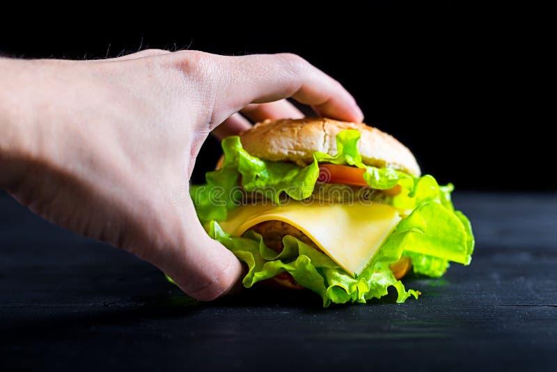Smakelijke en verse hamburger op een houten zwarte lijst, reclamebanner royalty-vrije stock fotografie