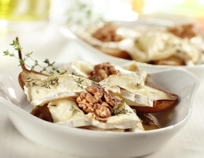 Smakelijke gebakken peer met de okkernoot en de thyme van de Briehoning royalty-vrije stock afbeeldingen