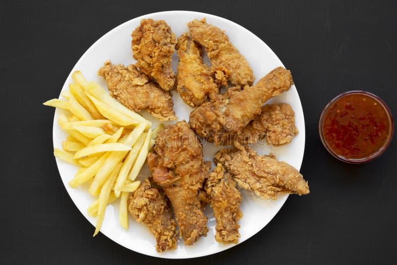 Smakelijke gebraden kippentrommelstokken, kruidige vleugels, Frieten, kippenvingers op witte plaat en saus over zwarte achtergron stock foto