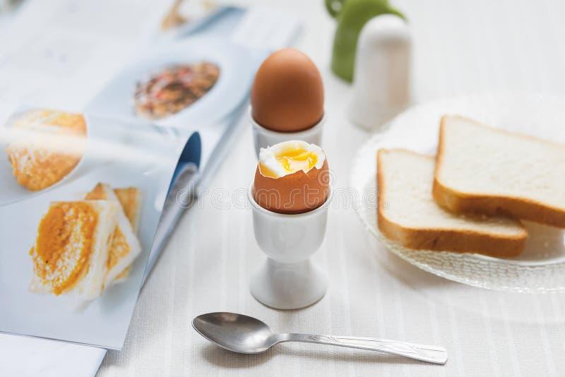 Smakelijke gekookte eieren voor ontbijt op de witte lijst stock afbeelding