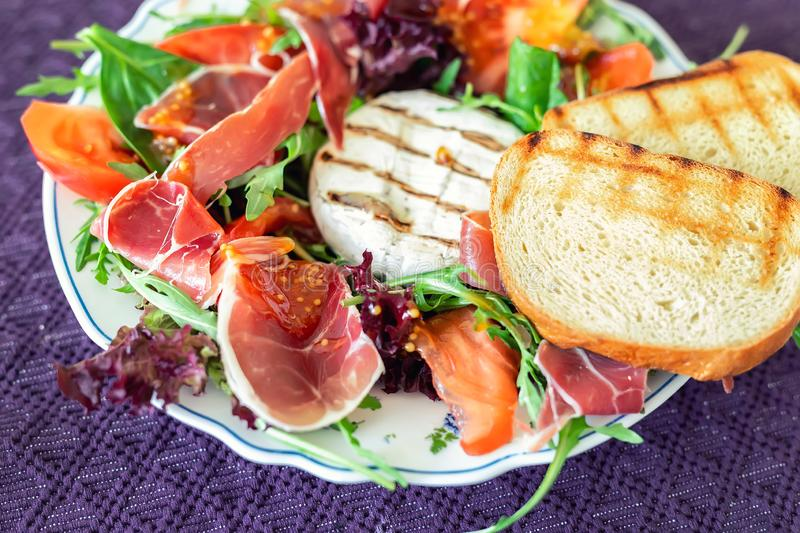 Smakelijke gemengde saladeschotel met geroosterde camembertkaas, prosciuttoham, organische tomaat en verse groene bladeren Gezond stock afbeelding