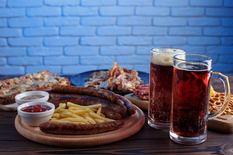 Smakelijke geplaatste biersnacks Varkensvleesplakken, geroosterd worsten en Fr stock afbeelding