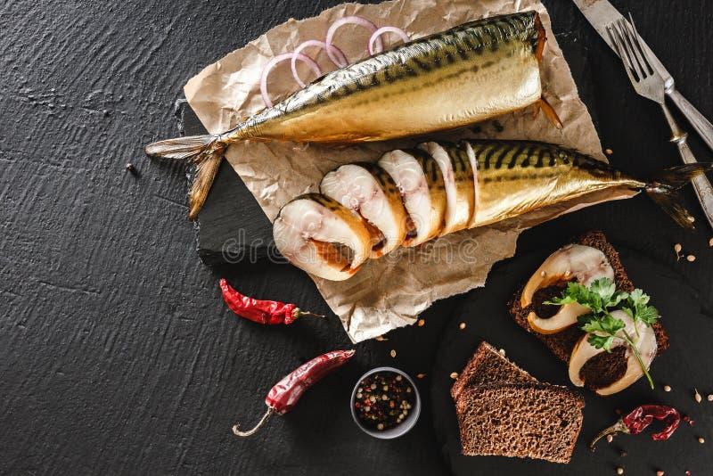 Smakelijke gerookte vissen met kruiden, bestek, peper en brood op ambachtdocument over donkere steenachtergrond Sandwich met gero stock foto's