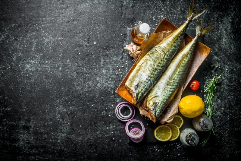 Smakelijke gerookte vissenmakreel met plakken van citroen, uiringen en kruiden stock afbeelding