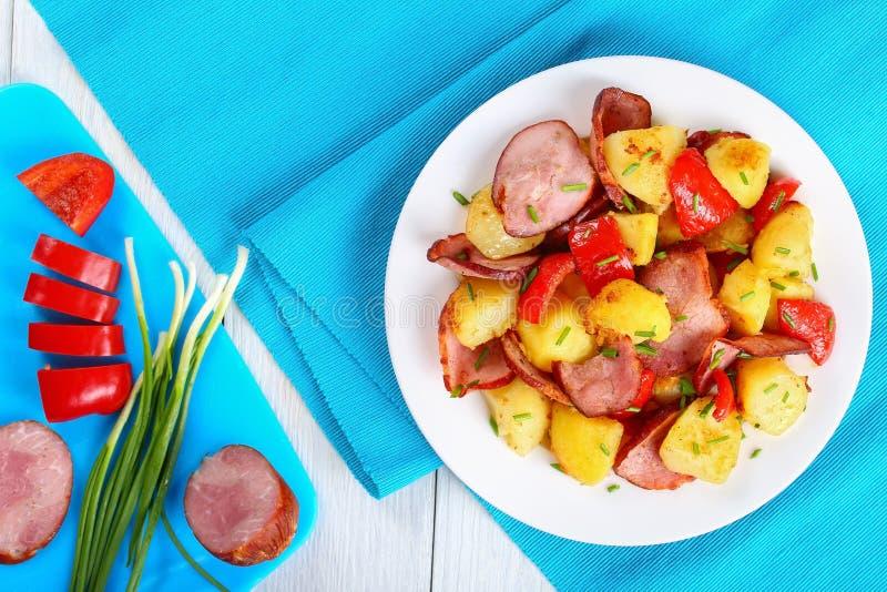 Smakelijke geroosterde aardappelwiggen met worsten stock afbeelding
