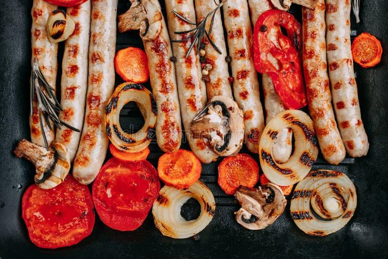 Smakelijke geroosterde die worsten en groenten in een het braden pa worden gediend stock afbeeldingen