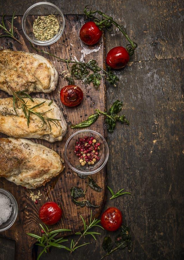 Smakelijke geroosterde kippenfilet met kruiden, kruiden, kruiden en tomaten op uitstekende uithalende raad over rustieke houten a stock afbeelding