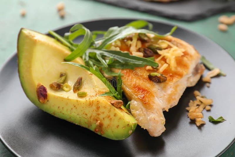 Smakelijke geroosterde kippenfilet met rijpe avocado op plaat, close-up royalty-vrije stock afbeelding