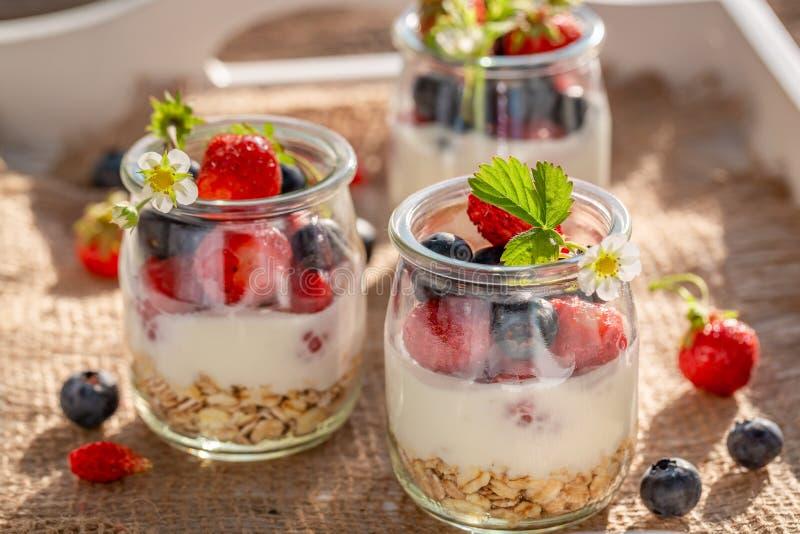 Smakelijke granola in kruik met yoghurt en bessen royalty-vrije stock foto's