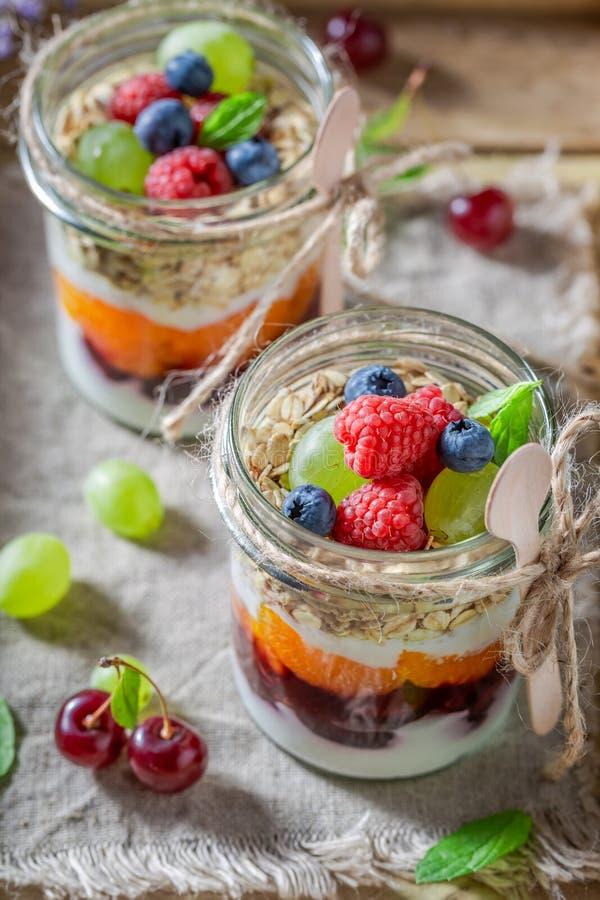 Smakelijke granola met verse bessen en yoghurt in kruik royalty-vrije stock fotografie