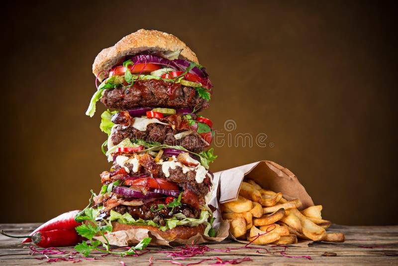 Smakelijke grote hamburger op houten lijst stock afbeeldingen