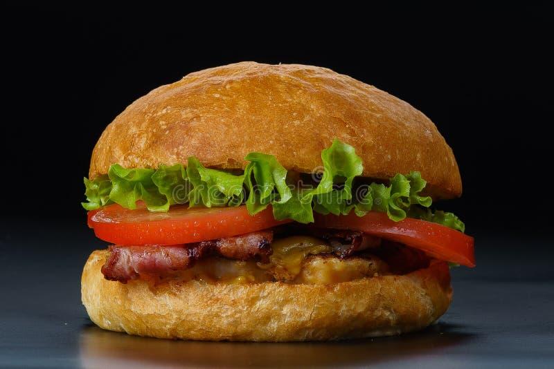 Smakelijke hamburger met bacon en tomaten royalty-vrije stock foto