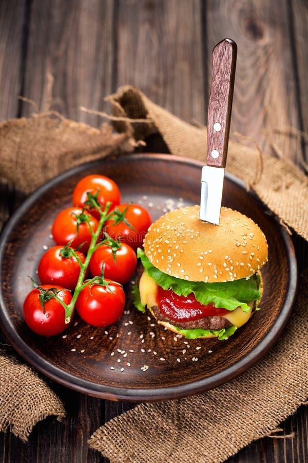 Smakelijke hamburger met tomaten op lijst stock foto