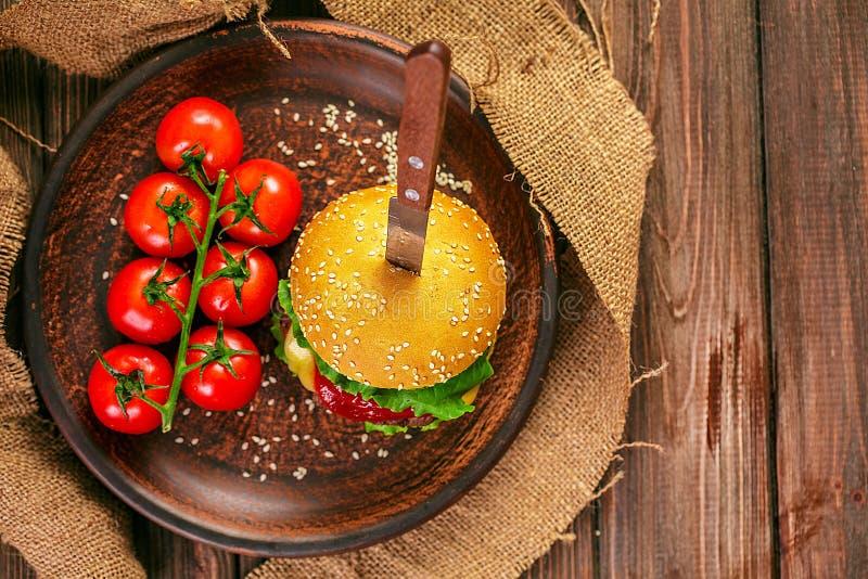 Smakelijke hamburger met tomaten op lijst stock afbeeldingen