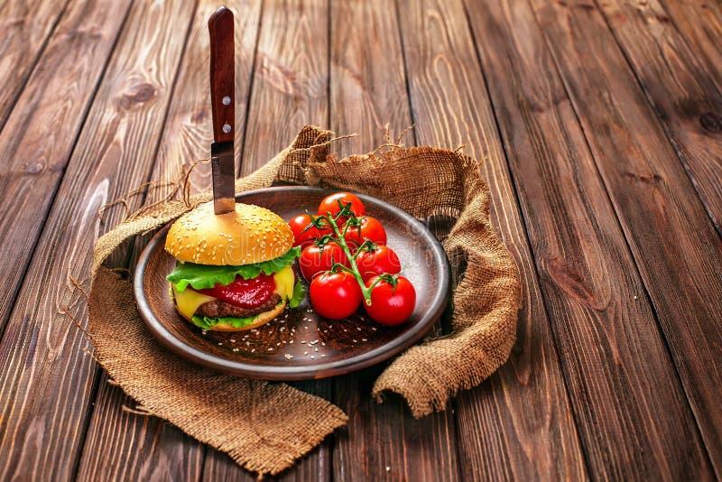 Smakelijke hamburger met tomaten op lijst stock fotografie