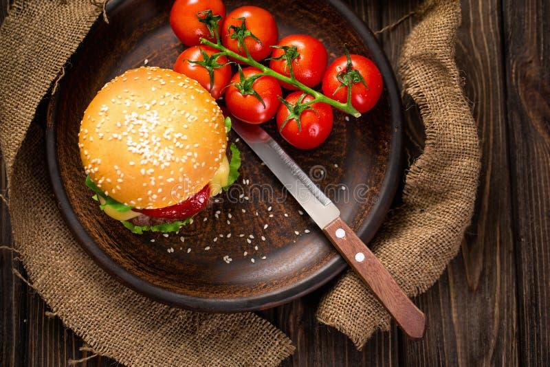 Smakelijke hamburger met tomaten op lijst royalty-vrije stock foto's