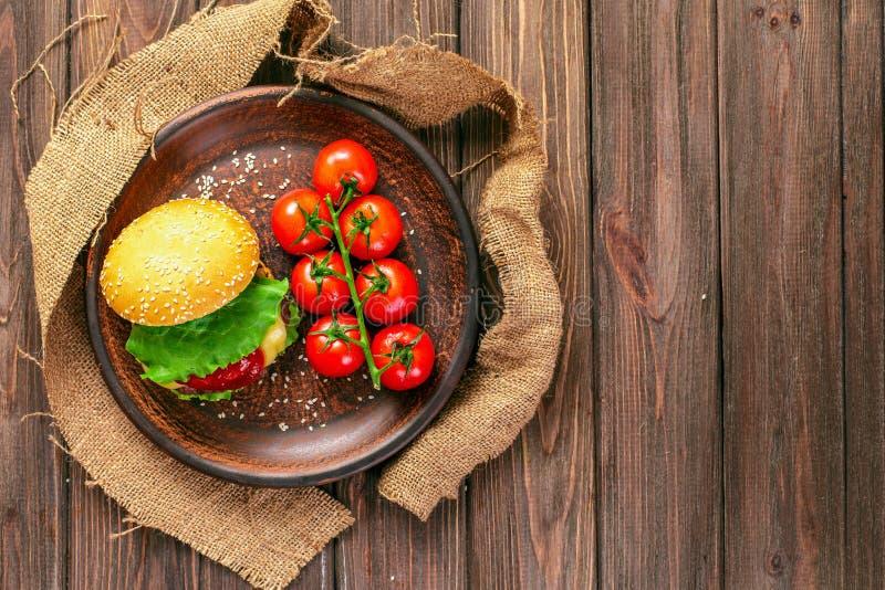 Smakelijke hamburger met tomaten op lijst royalty-vrije stock foto
