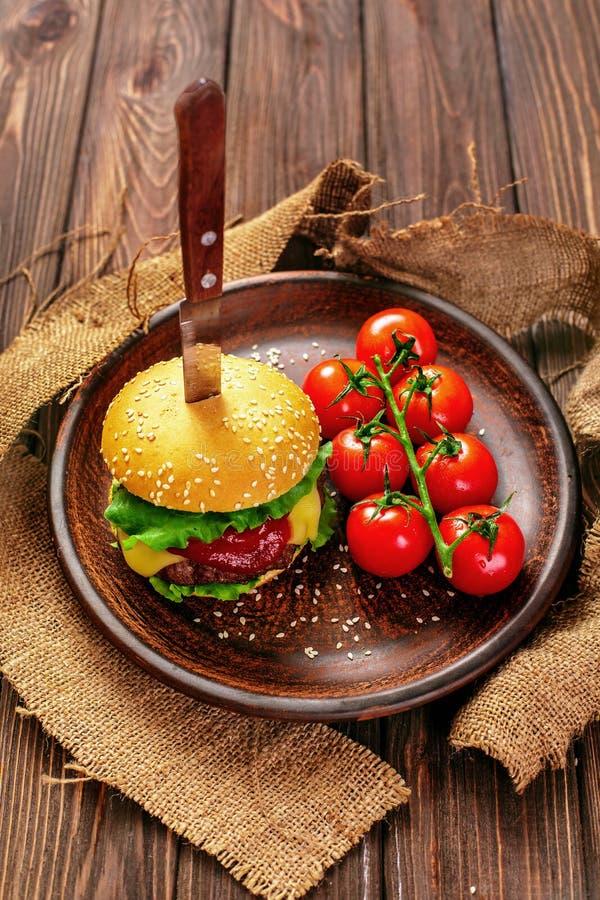 Smakelijke hamburger met tomaten op lijst royalty-vrije stock afbeeldingen