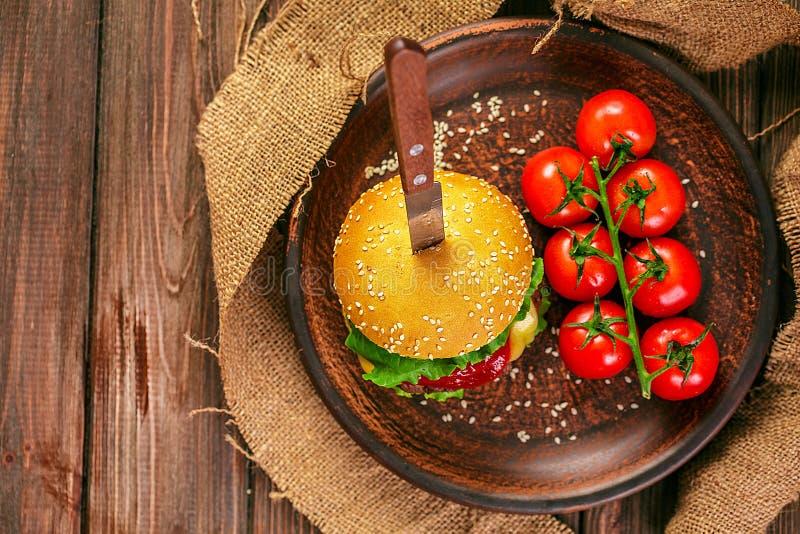 Smakelijke hamburger met tomaten op lijst stock foto's