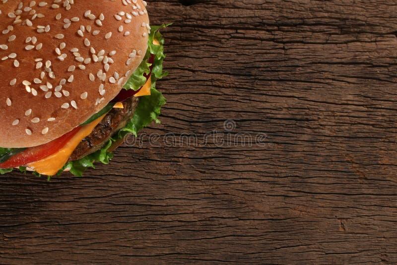 Smakelijke hamburger op houten achtergrond stock fotografie