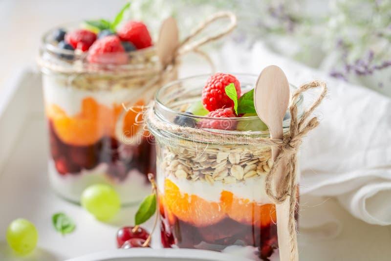 Smakelijke havervlokken in kruik met yoghurt en verse bessen stock afbeeldingen