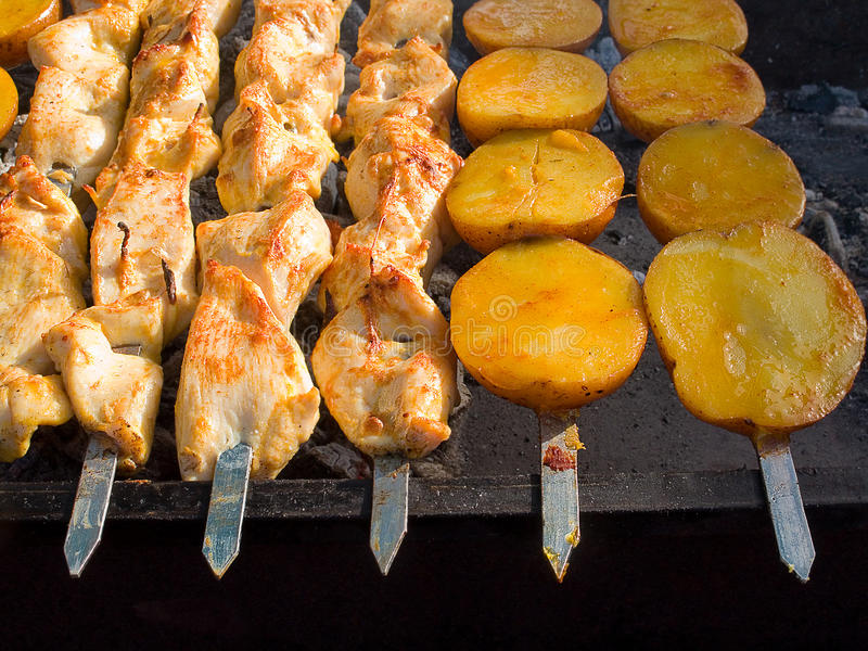 Smakelijke heerlijke gebraden vlees en aardappels op een barbecuegrill in openlucht stock foto's