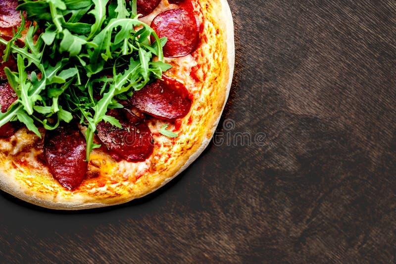 Smakelijke Hete Italiaanse die pizza met pepperonis op oud houten lusje worden gediend stock fotografie