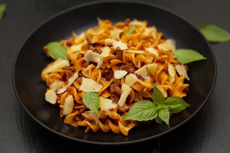 Smakelijke smakelijke klassieke Italiaanse Fusilli-deegwaren met tomatensaus, kaasparmezaanse kaas, rundvlees en basilicum in zwa stock afbeeldingen