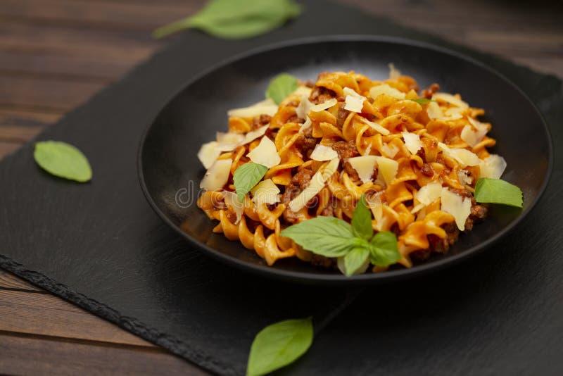 Smakelijke smakelijke klassieke Italiaanse Fusilli-deegwaren met tomatensaus, kaasparmezaanse kaas, rundvlees en basilicum in zwa royalty-vrije stock foto