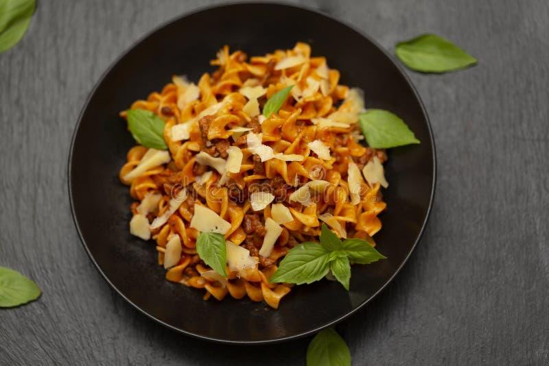 Smakelijke smakelijke klassieke Italiaanse Fusilli-deegwaren met tomatensaus, kaasparmezaanse kaas, rundvlees en basilicum in zwa stock foto's