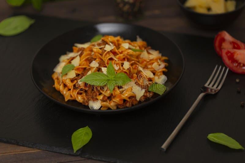 Smakelijke smakelijke klassieke Italiaanse Fusilli-deegwaren met tomatensaus, kaasparmezaanse kaas, rundvlees en basilicum in zwa stock afbeelding