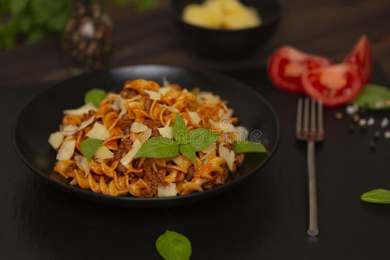 Smakelijke smakelijke klassieke Italiaanse Fusilli-deegwaren met tomatensaus, kaasparmezaanse kaas, rundvlees en basilicum in zwa royalty-vrije stock foto's