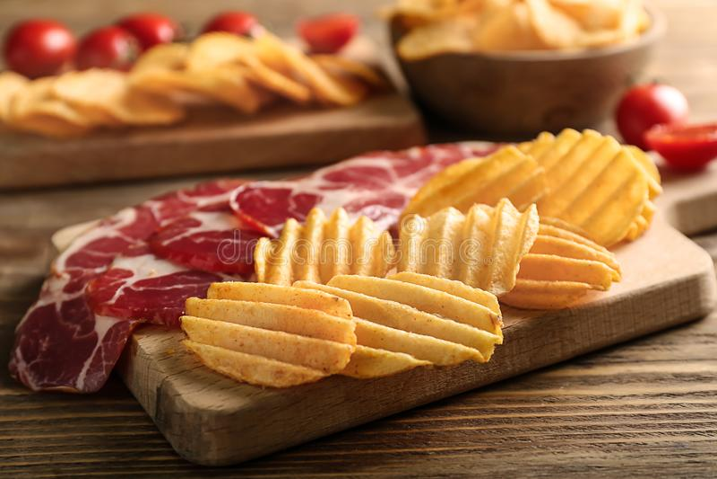Smakelijke knapperige chips met bacon op houten raad stock foto's
