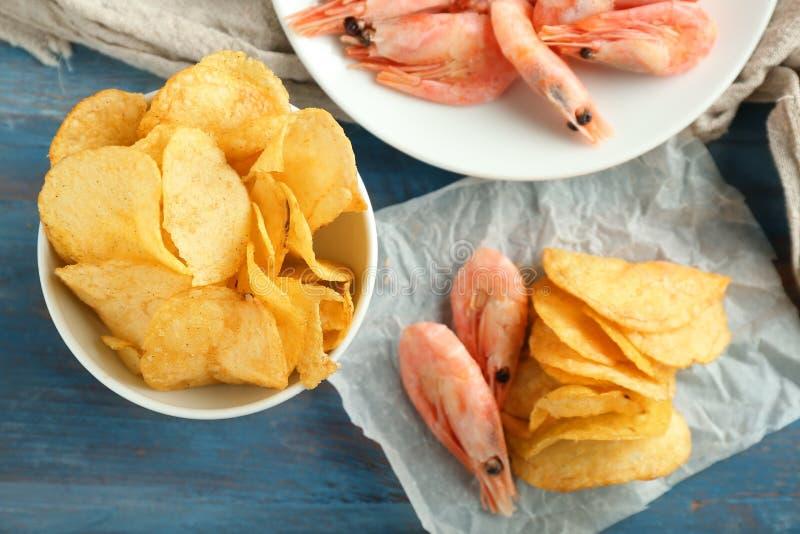 Smakelijke knapperige chips met garnalen op kleuren houten lijst stock afbeeldingen